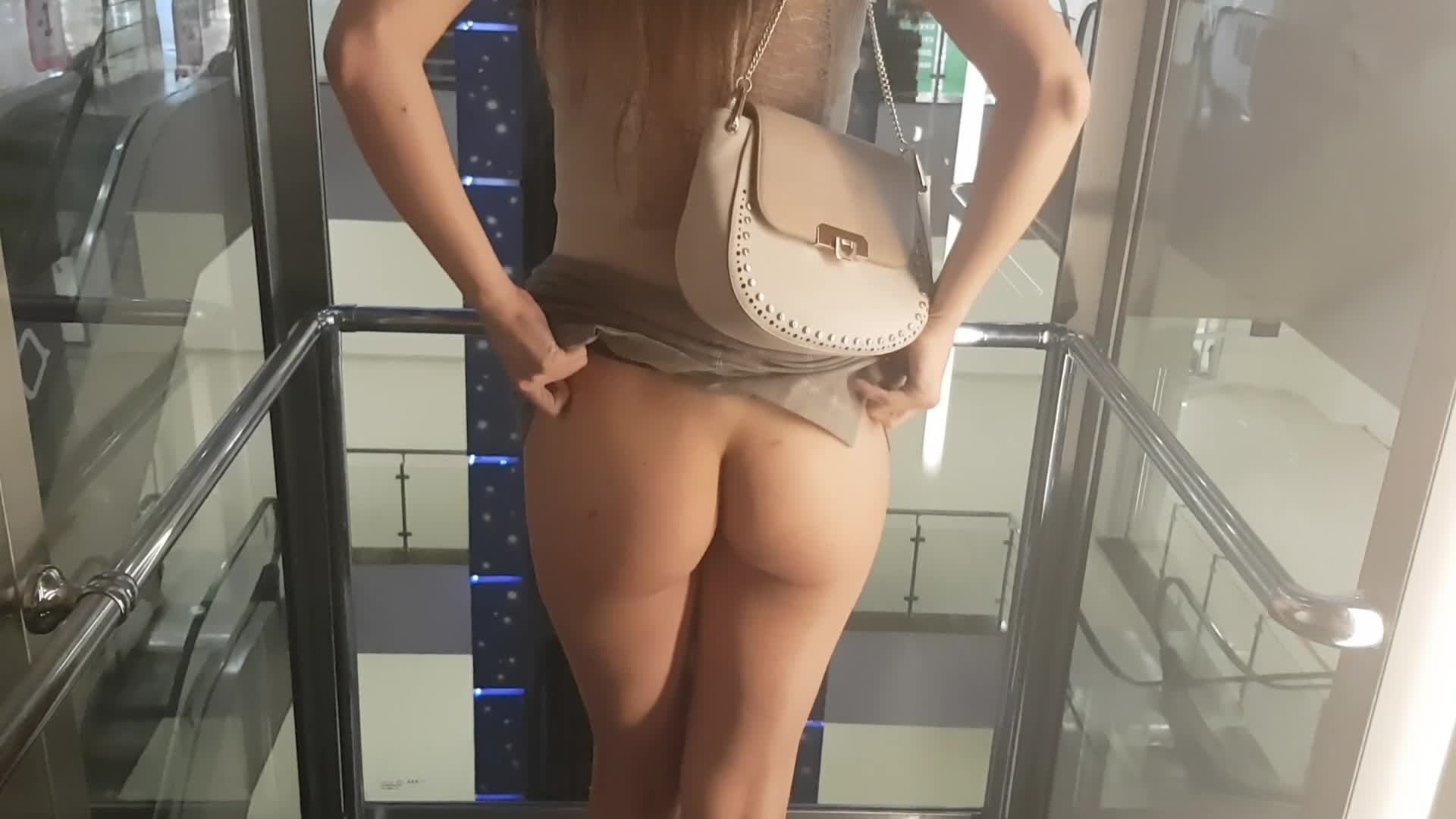 Woman in skirt shows ass and boobs in transparent elevator